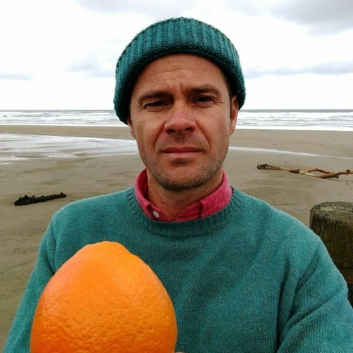 Featured author Roger Peet posing on beach with an orange.