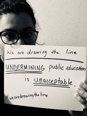 """Person We are Drawing the Line Selfie half of their face with a handwritten sign that says """"We are drawing theline. UNDERMINING public education is UNACCEPTABLE. #wearedrawingtheline"""""""