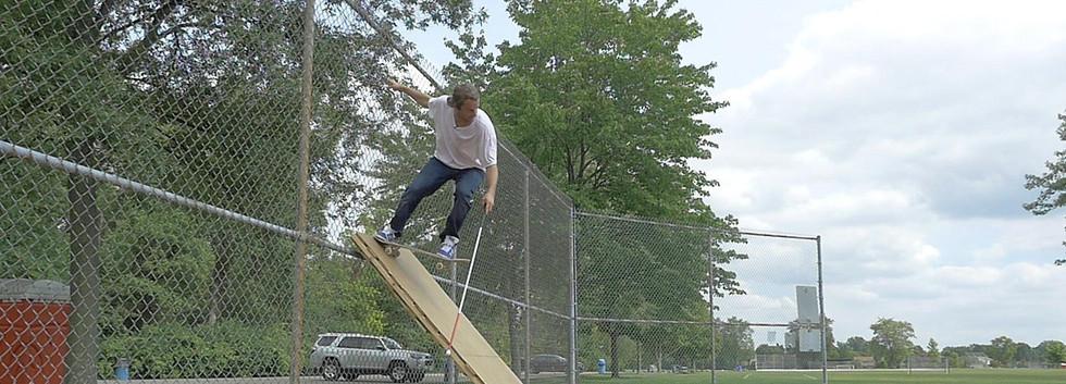 dan mancina dropping in on a makeshift ramp at a park