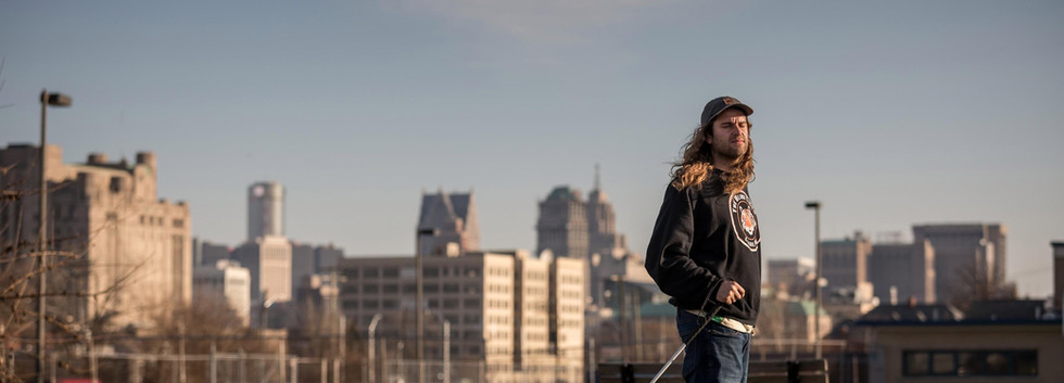 dan mancina with skateboard with detroit skyline in background