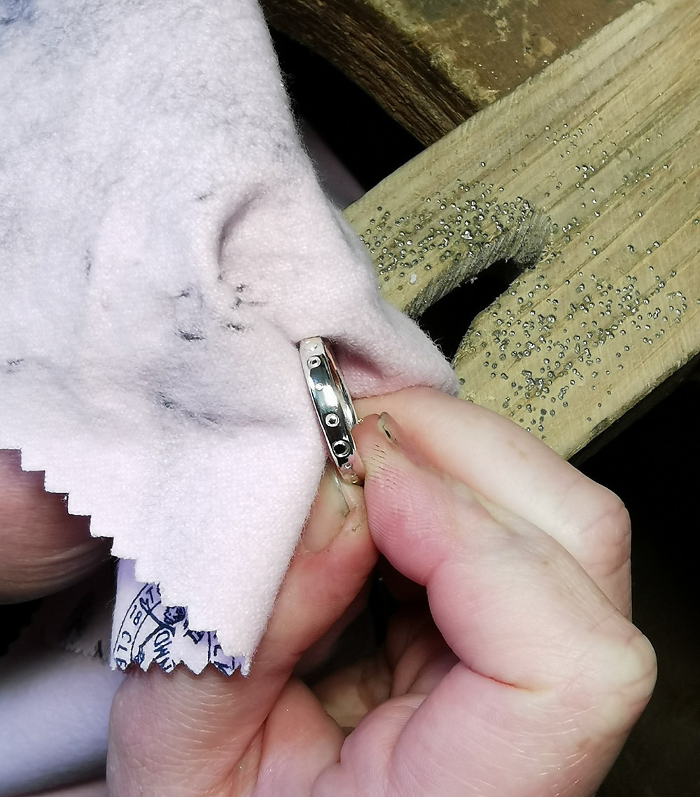 Using a silver cloth to polish a sterling silver ring