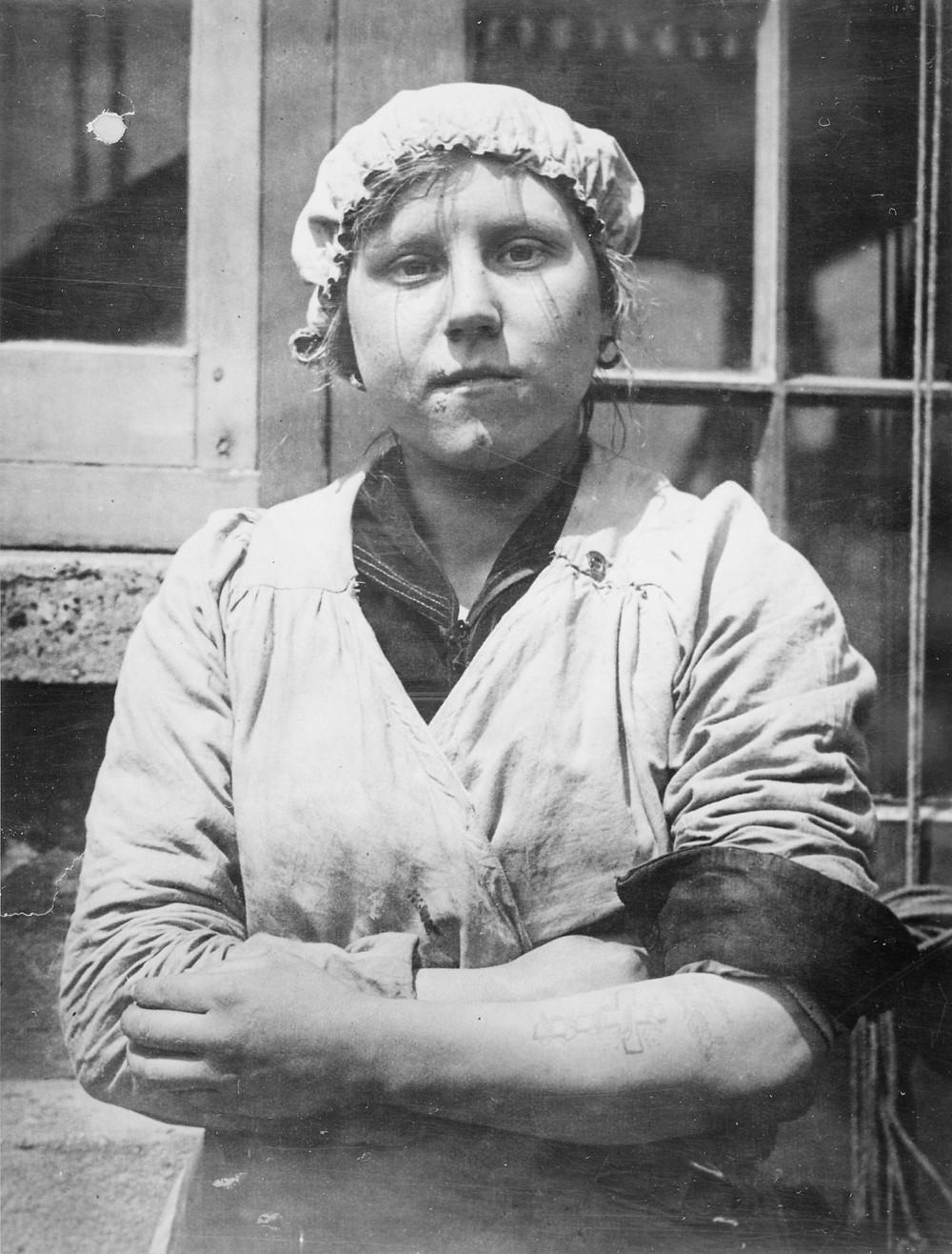 Trabalhadora, na fabricação de munição, com uma tatuagem no braço esquerdo, com o nome de um ente querido que morreu na guerra. A cruz memorial foi adicionada mais tarde