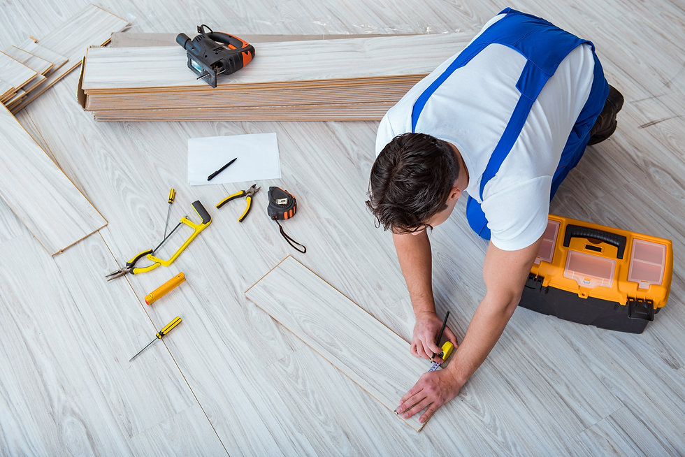 Repairman laying laminate flooring at ho