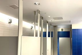 Grey, blue, and white bathroom at a high school containing Zeptive vape detectors in the stalls
