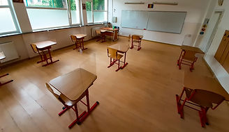 Empty and dark classroom with tan desks and a clean whiteboard