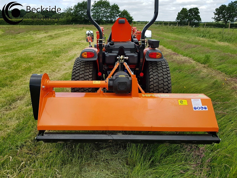 A flail mower attached to a compact tractor