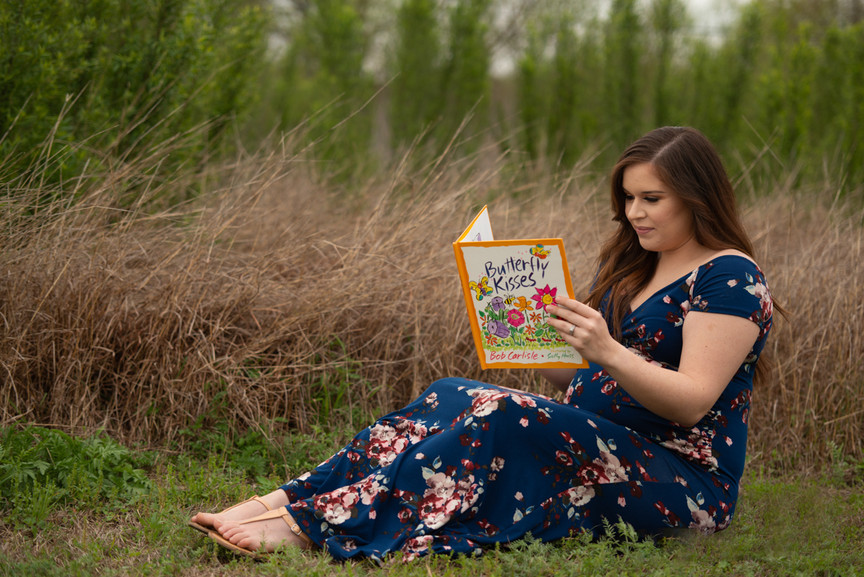Woman reads childhood storybook while pregnant