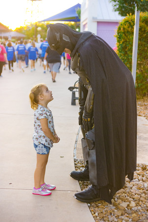 Little girl looks up to talk to Superher
