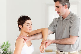 Massage therapist providing thai arm stretch to recipient