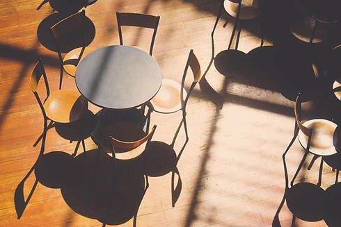 A few chairs and tables in a sunlit room
