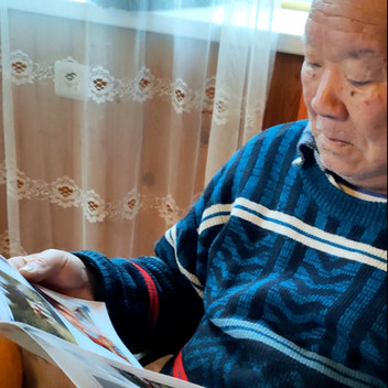Grandfather reading monthly family journal