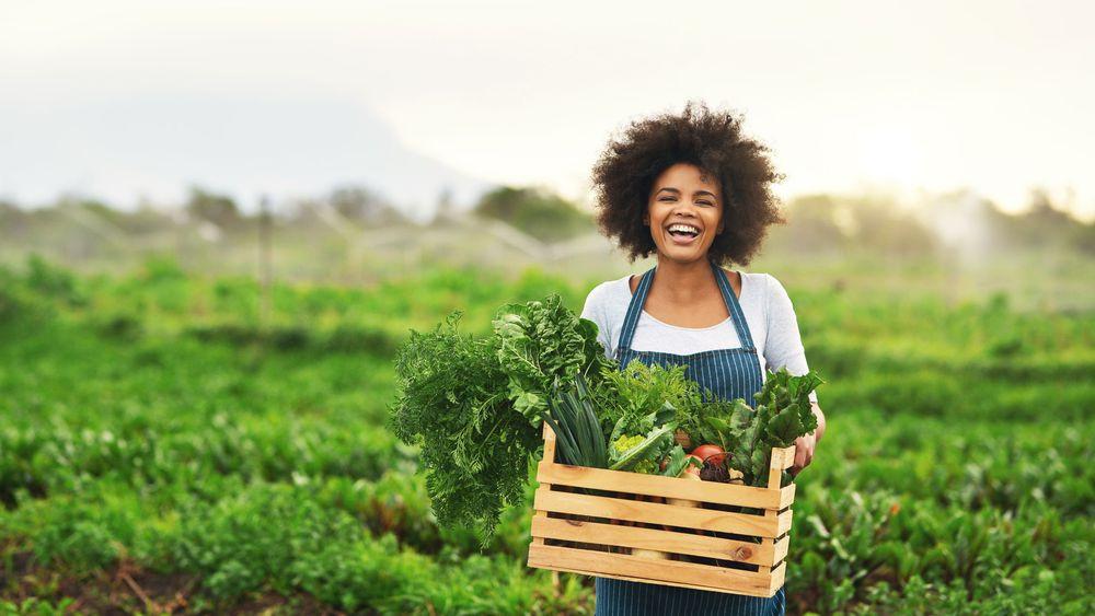 Femme qui tient un panier de légumes