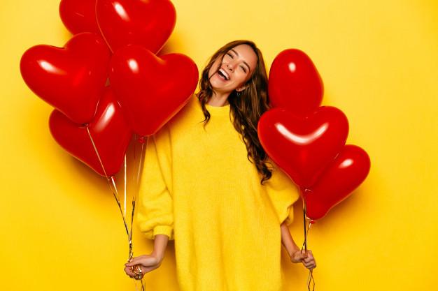 jeune femme heureuse, souriante avec des ballons en forme de coeur rouge