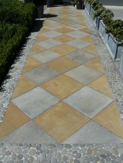 Pebble mosaic border around pavers