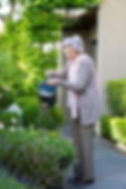 Barbara Matthews watering her beloved garden