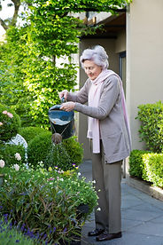 Barbara Matthews watering her beloved garden