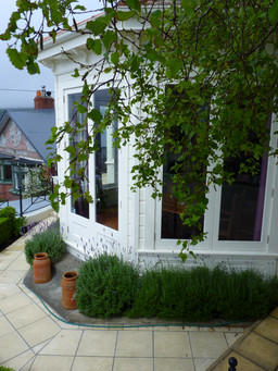 Narrow front garden wrapped around house