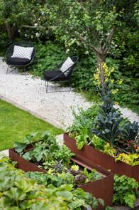 White pebble paths, black seats & corten planters