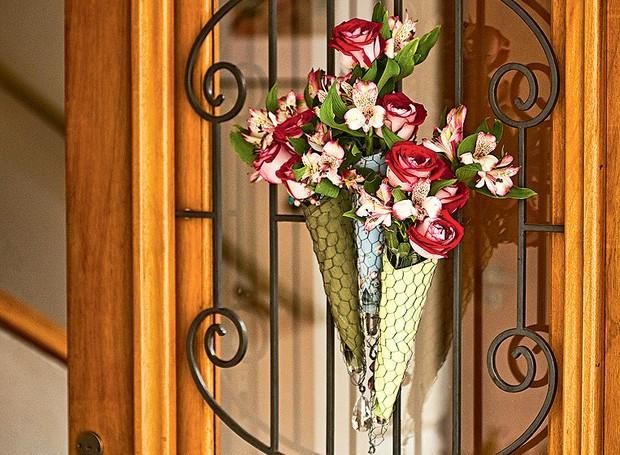 Flores são um forte amuleto contra energias ruins. Use na casa toda! Nesta porta de entrada, Claudia Regina, da La Calle Florida, fez um buquê com rosas e astromélias envolvidas em guardanapo e tela de galinheiro (Foto: Editora Globo)