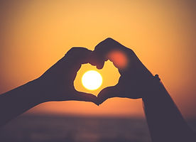 Hands form the shape of a heart and frame the sun during a sunset.
