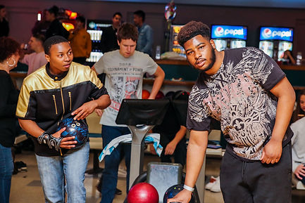 Three teenagers prepare to bowl at a Freda Fund bowling party.