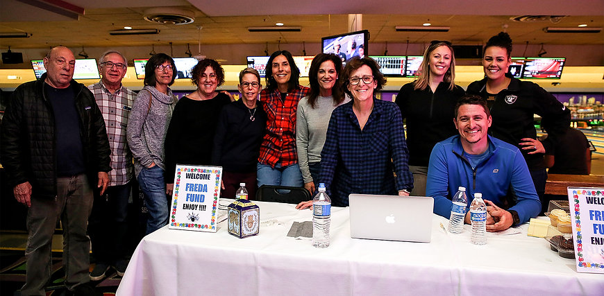 Freda Fund staff and volunteers welcome guests to a bowling birthday party celebration at the registration table.
