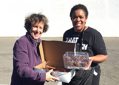 Phyllis Needelman and Terri from Terri Does Desserts hold boxes with a birthday sheet cake and cupcakes.