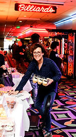 Phyllis Needelman puts cupcakes out for guests at a birthday party.