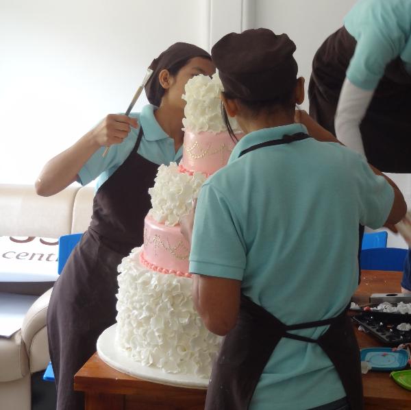 Girls working on a wedding cake