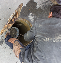 A man working on a sewer drain