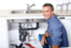 A Plumber in front of  kitchen sink drain