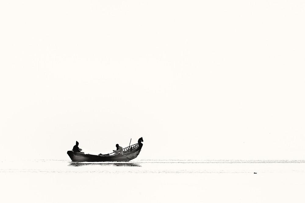 Dos personas dentro de un bote en el agua.