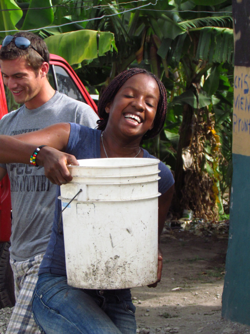 Blondine helping by bringing water for cement mixing