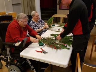Glazenwassers ACW helpen ouderen met kerststukje maken