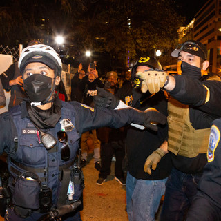 A D.C. Metropolitan Police Department officer tries to keep members of the Proud Boys, dressed in their signature black and yellow, separated from counter-protesters on Saturday, December 12, 2020.