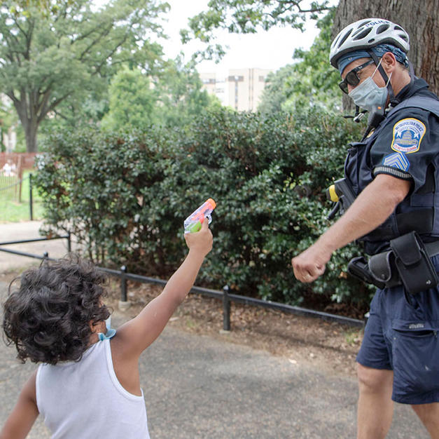 A child points a water gun at a D.C. Metro Police Department bike patrol officer as the officer goes in for a fist bump at Malcolm X Park in Washington, D.C. on Saturday, August 8 before a D.C. Protests' march.