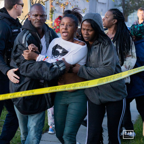 I woman is restrained after rushing under the police tape at the cite of a murder at the corner of St. James and Religious street in New Orleans, LA on Tuesday, November 20. One man was found shot in the chest around 3 PM. (Zach Brien, UptownMessenger.com)