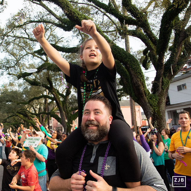 Troy Never lifts his daughter Ellie up to reach for beads from the captain's float during the Krewe of Endymion in 2019.