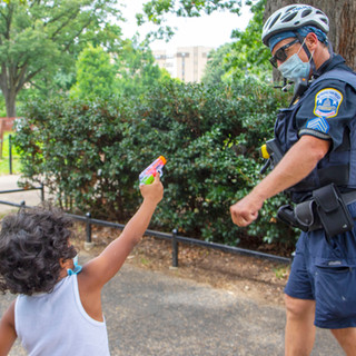 A young child squirts a water gun at D.C. Metropolitan Police Department officer Timothy E. Evans in Malcolm X. Park on Saturday, August 8, 2020.
