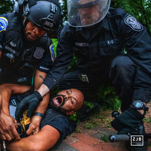 A man is detained by a D.C. Metropolitan Police Department officer and a U.S. Secret Service officer on June 22, 2020 as protesters attempted to pull down the statue of President Andrew Jackson in the park.