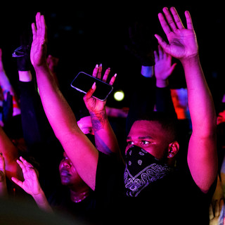 Protesters put up their hands, showing they pose no threat, as they surround a U.S. Capitol Police Officer vehicles outside of the Capitol building on Friday, May 29, 2020.