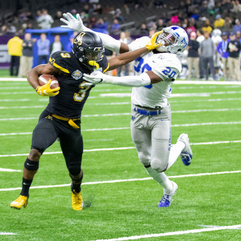 Darryton Evans, Appalachian State University running back,  stiff-arms Middle Tennessee State University linebacker D.Q. Evans on his way to the endzone during the R&L Carriers New Orleans Bowl on December 15, 2018. Appalachian State beat Middle Tennessee 45-18.