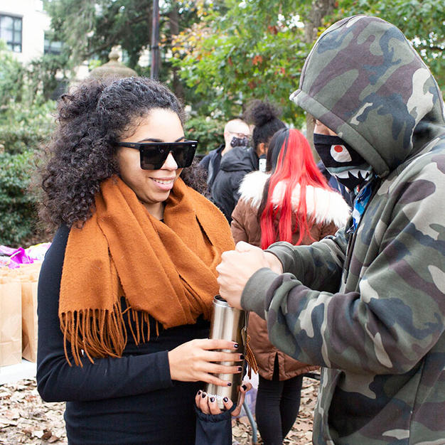 Justin warms his hands over Brittany's cup of tea before D.C. Protests' left Malcolm X Park on Saturday, October 31.