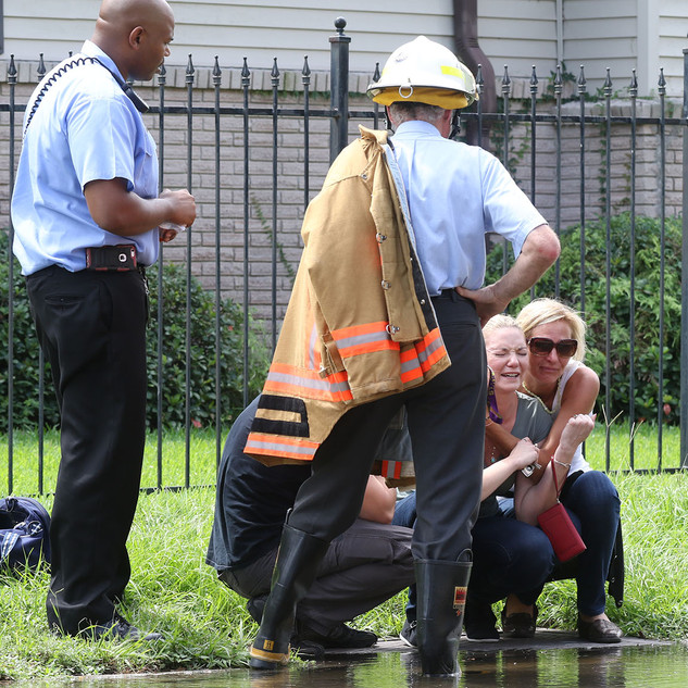 A woman is consoled by fire officials at the scene of a four-alarm fire in the 4200 block of Rocheblave street in New Orleans' Broadmoor neighborhood on September 15, 2016.