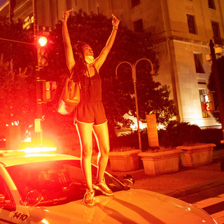 A protester hops on the hood of a D.C. Metro Police Department cruiser during a FTP march with the They/Them Collective along Constitution Avenue on Saturday, July 25, 2020