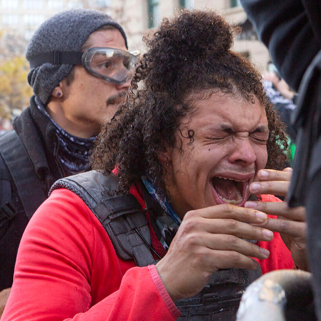 D.C. Protests co-founder Justin Daniels reacts to being pepper-sprayed by officers from the D.C. Metro Police Department on I Street NW on Saturday, December 12.