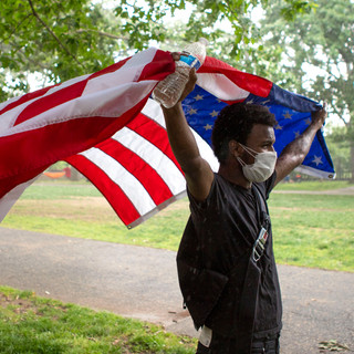 A protester raises an American flag in the rain and wind in Malcolm X Park on Saturday, June 6, 2020.