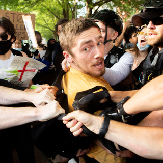 U.S. Secret Service officers and protesters struggle as the officers try to detain the man in yellow in Lafayette Square Park on Friday, May 29 during a protest after the death of George Floyd in Minneapolis, MN.
