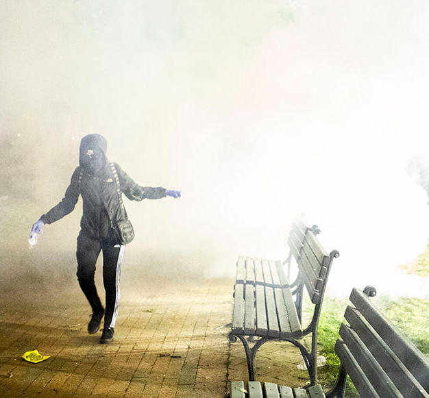 A protester emerges from a cloud of tear gas fired by U.S. Park Police in Lafayette Square Park in Washington, D.C. on Sunday, May 31. Law enforcement repeatedly fired tear gas, pepper spray, flash-bang grenades and other dispersants in an attempt to control the crowd around the White House during the days of protests after the death of George Floyd.