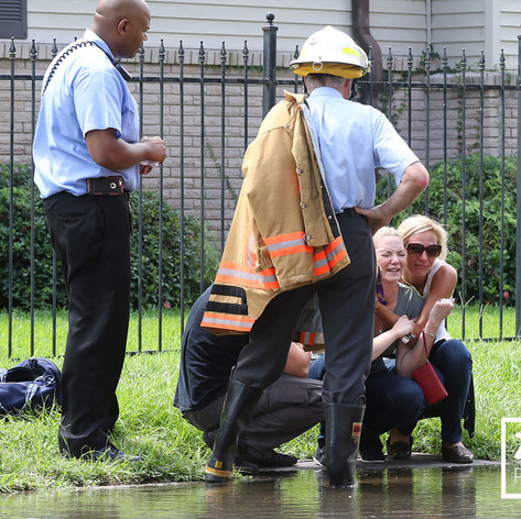 A woman is consoled by police and fire officials on the scene of a house fire in New Orleans' Broadmoor neighbrohood on September 16, 2016. The fire consumed two homes. (Zach Brien, UptownMessenger.com)